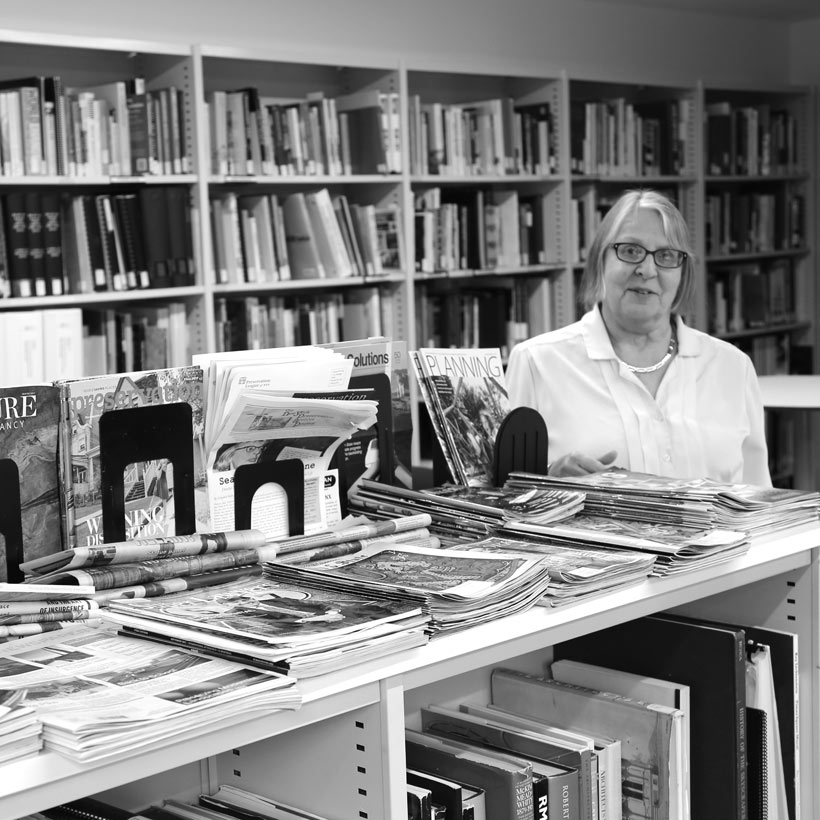 librarian with books in the Greenacre Reference Library