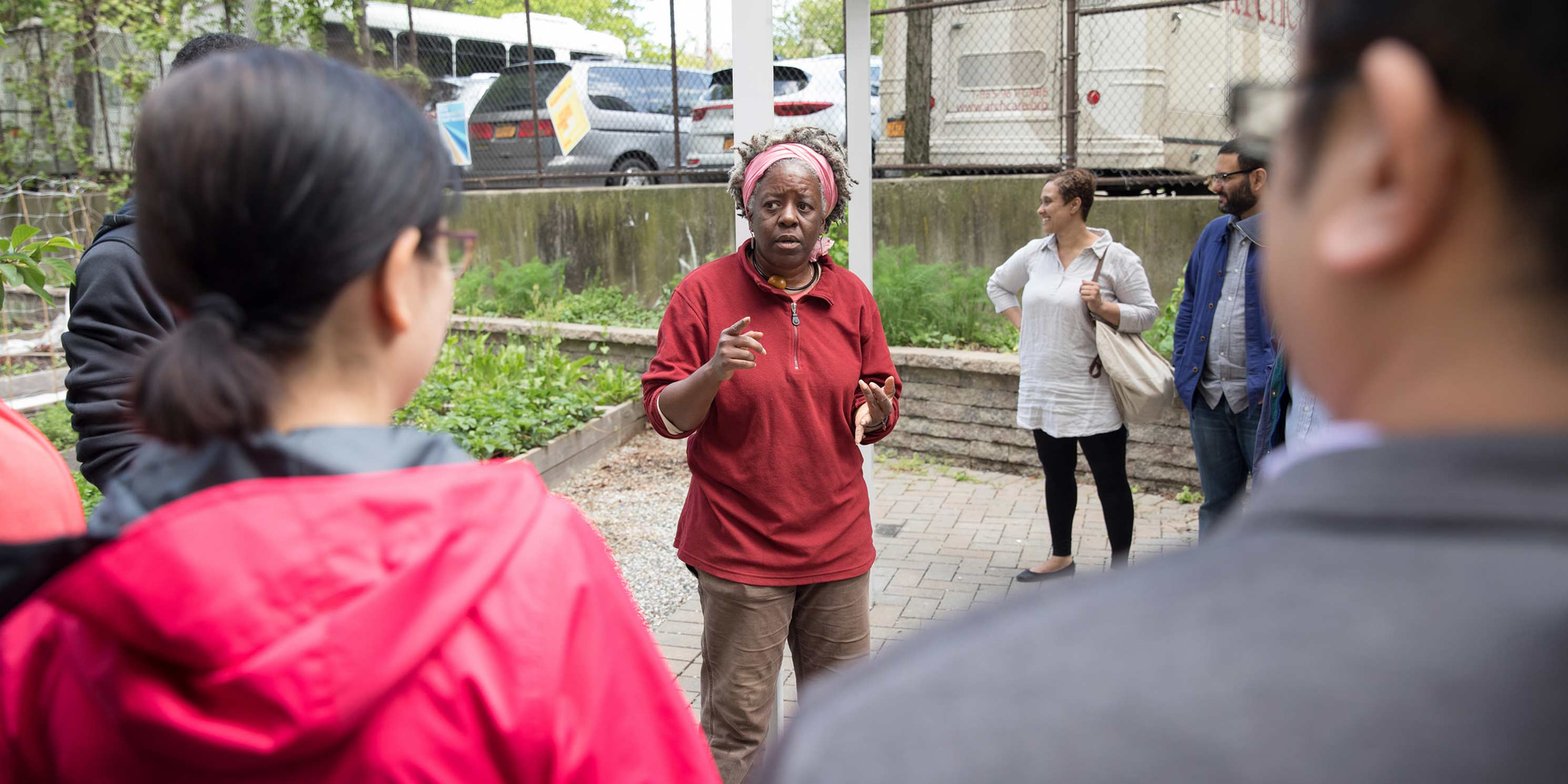 leader speaks during a Jane's Walk at a community garden