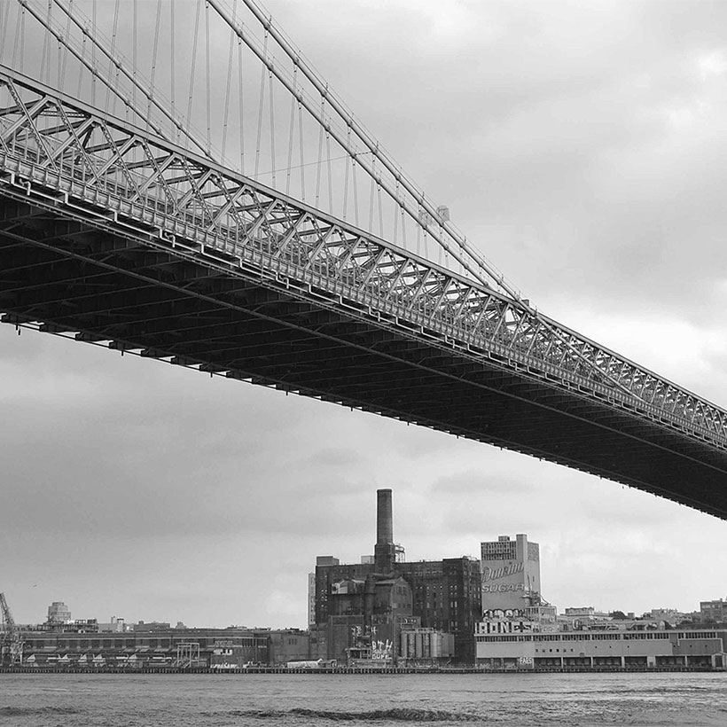 Williamsburg Bridge with the Domino Sugar Refinery in the background. Photo: Wikimedia Commons, Joe In Queens.
