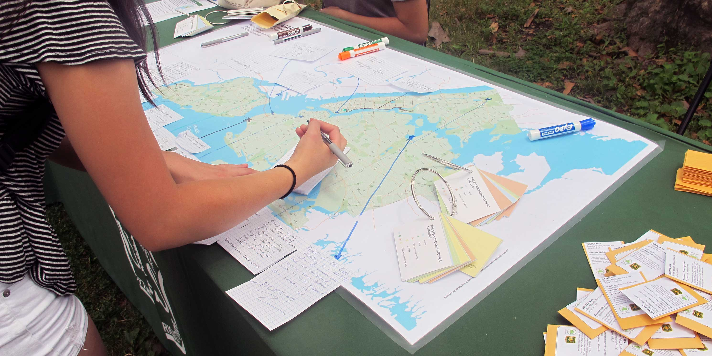 A woman draws on a map at a US Forest Service Urban Ranger Station in New York City