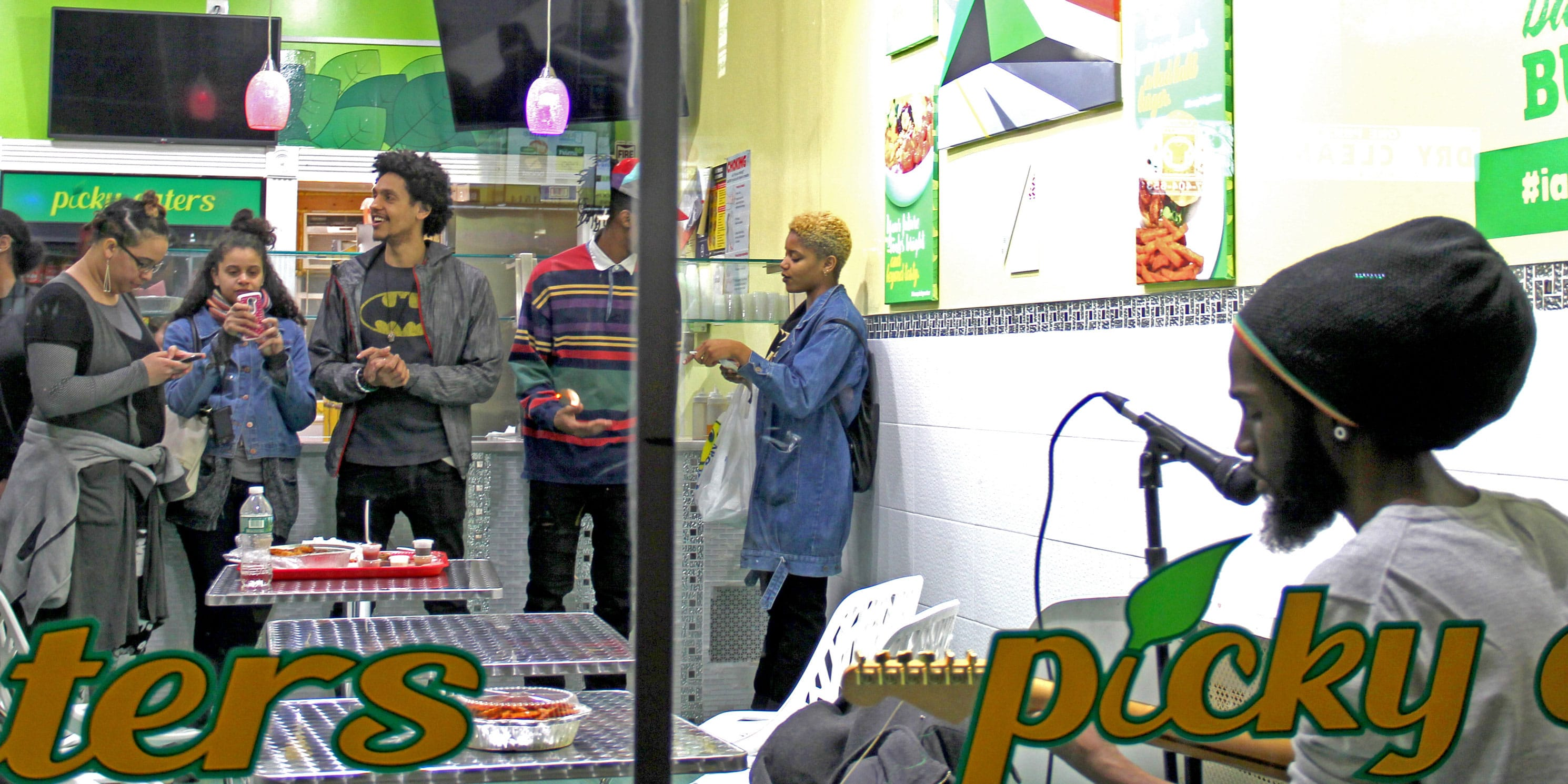 people listen to a musician in a takeaway food shop