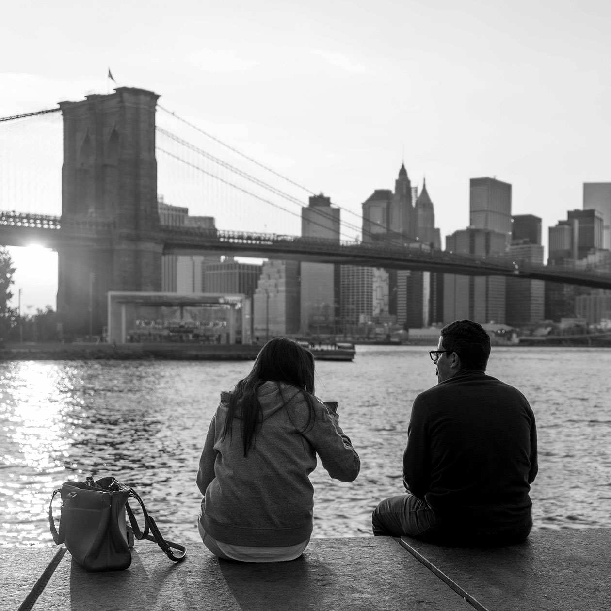 a couple sits in the park, near the Brooklyn Bridge