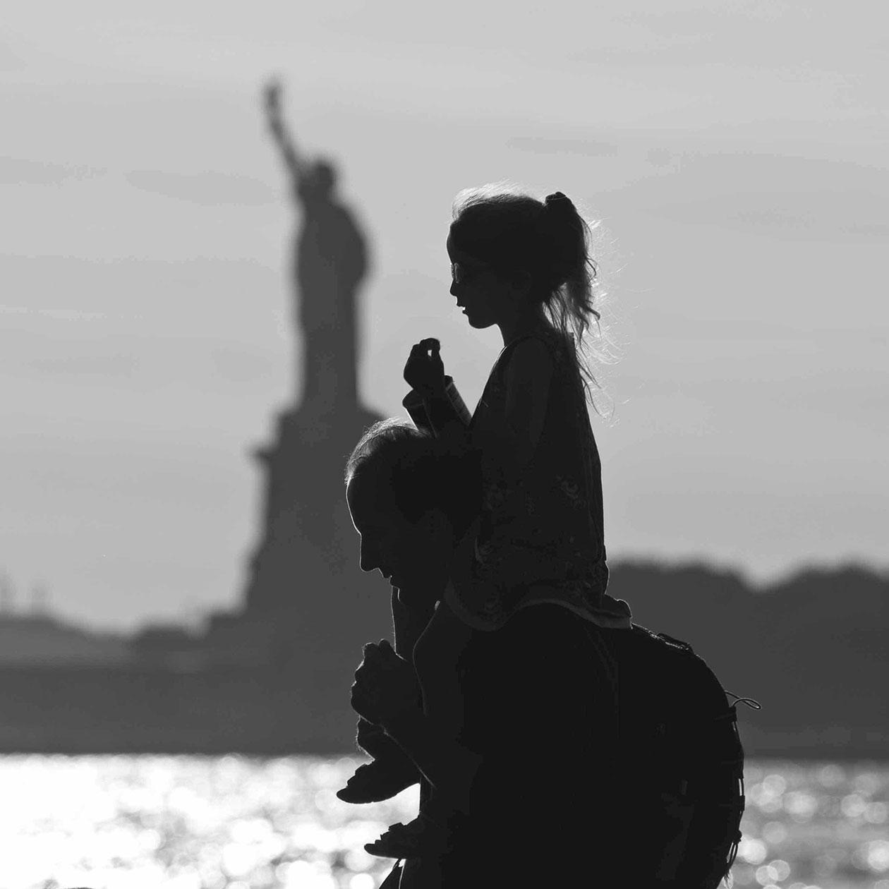 daughter on father's shoulders with Statue of Liberty in background