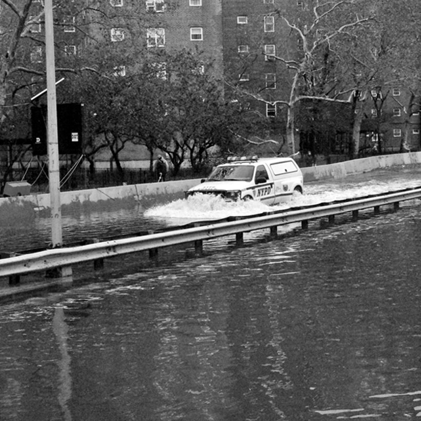 A NYPD van drives down the FDR flooded from Hurricane Sandy in 2012