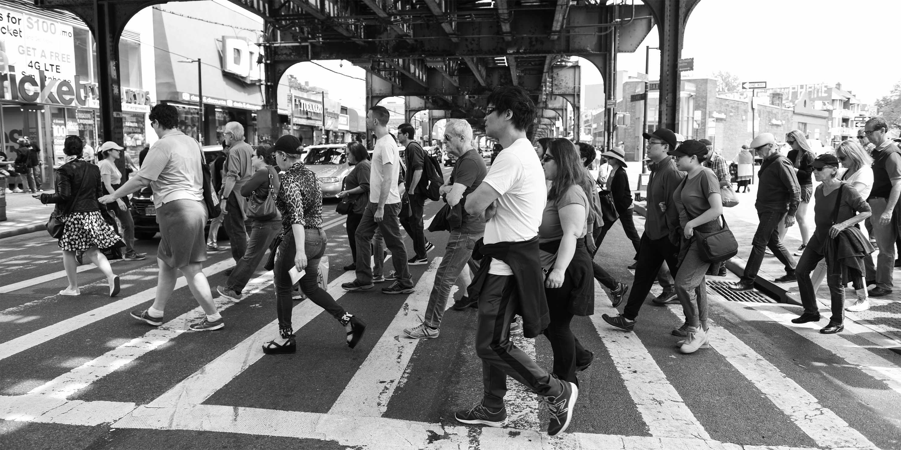 people on a Jane's Walk cross Roosevelt Avenue