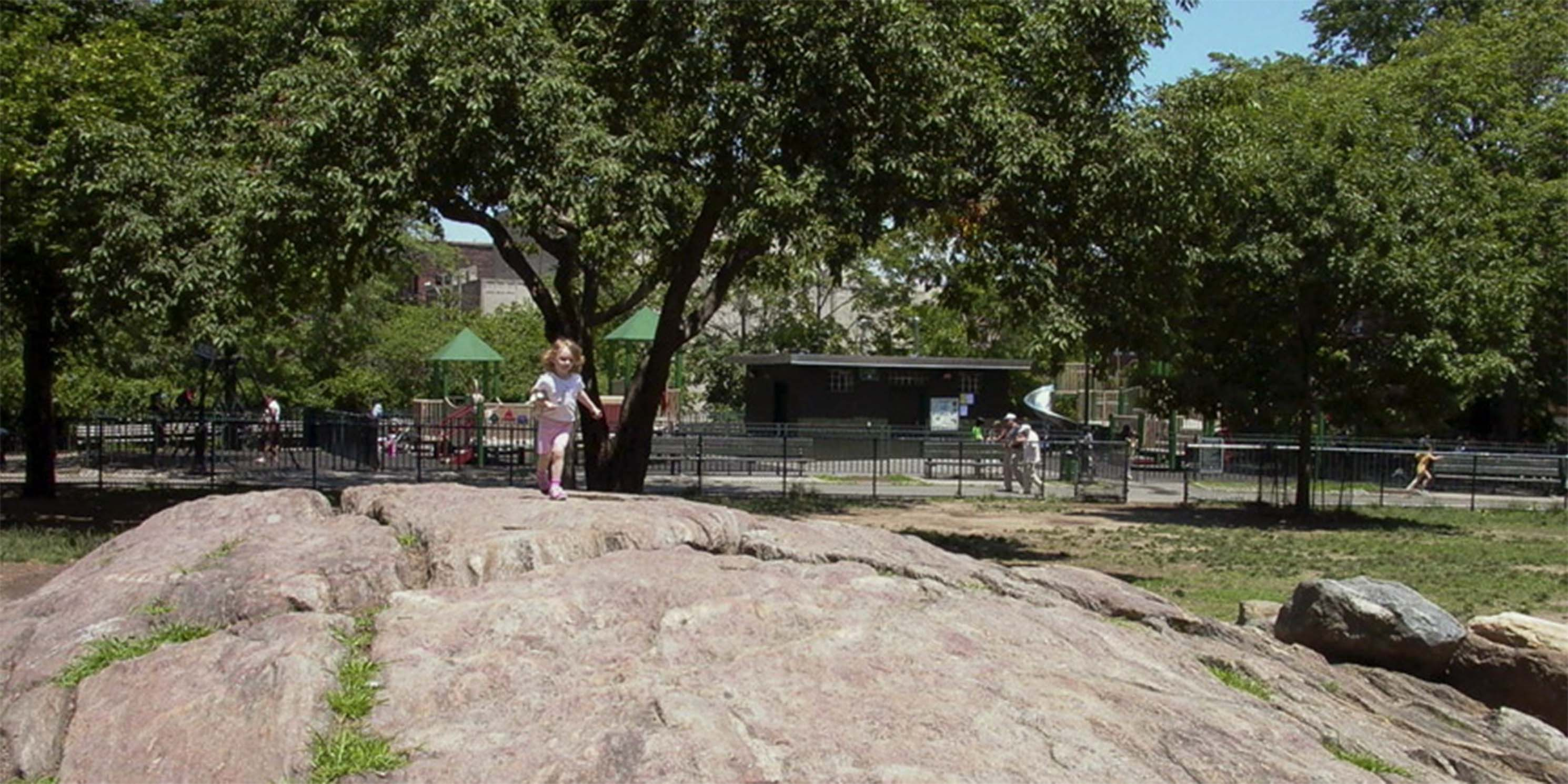 Child climbing rock in Bennett Park