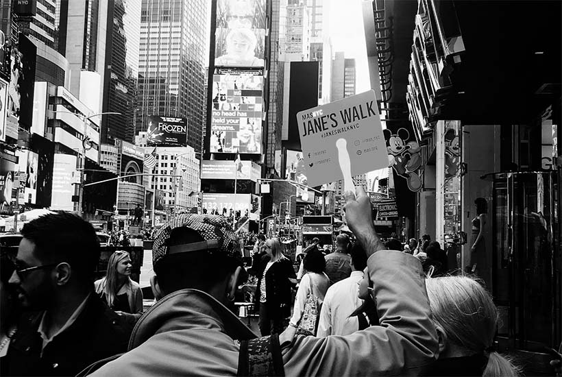 leader holds sign on Jane's Walk in Times Square