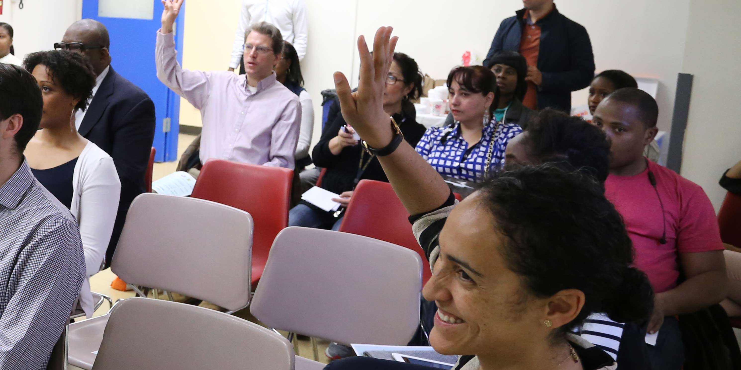 people raise hands at workshop