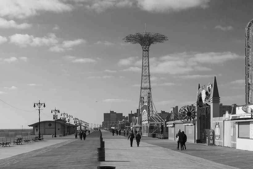 People walk the Riegelmann Boardwalk in Coney Island