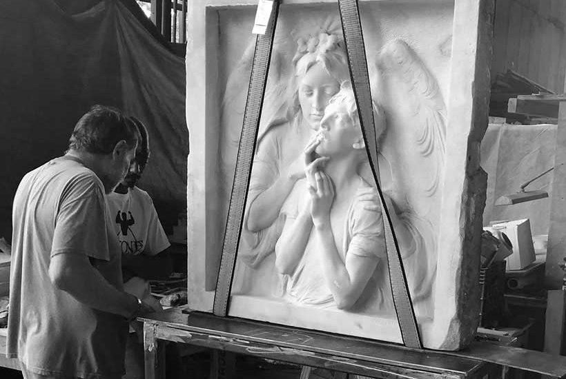 workers in a workshop stand near the restored Rebecca Salome Foster Memorial