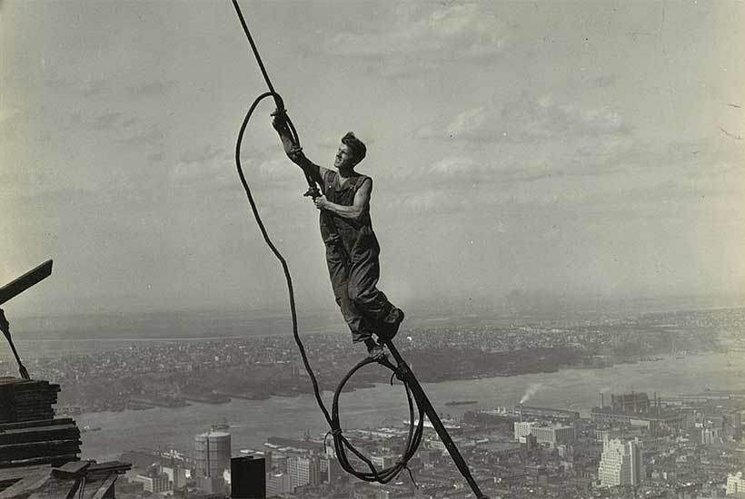 construction worker hangs on wire while building the Empire State Building
