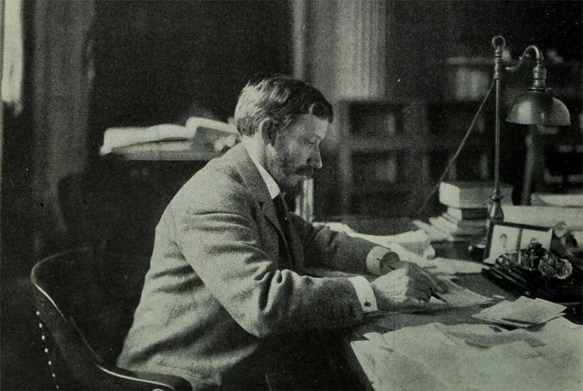 George McAneny writing at desk
