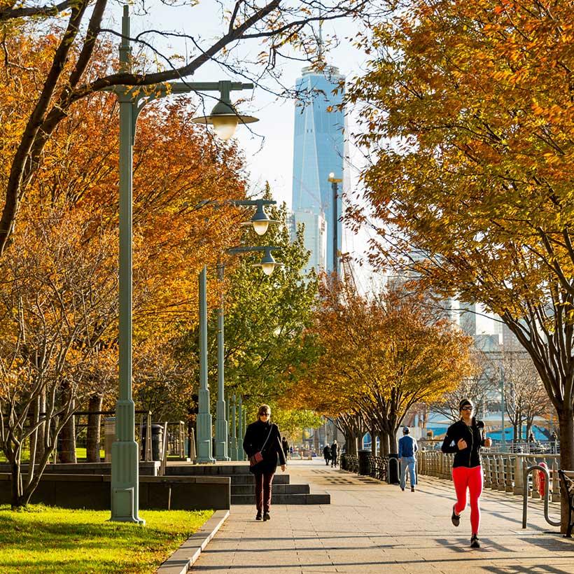 joggers run through Hudson River Park in Autumn