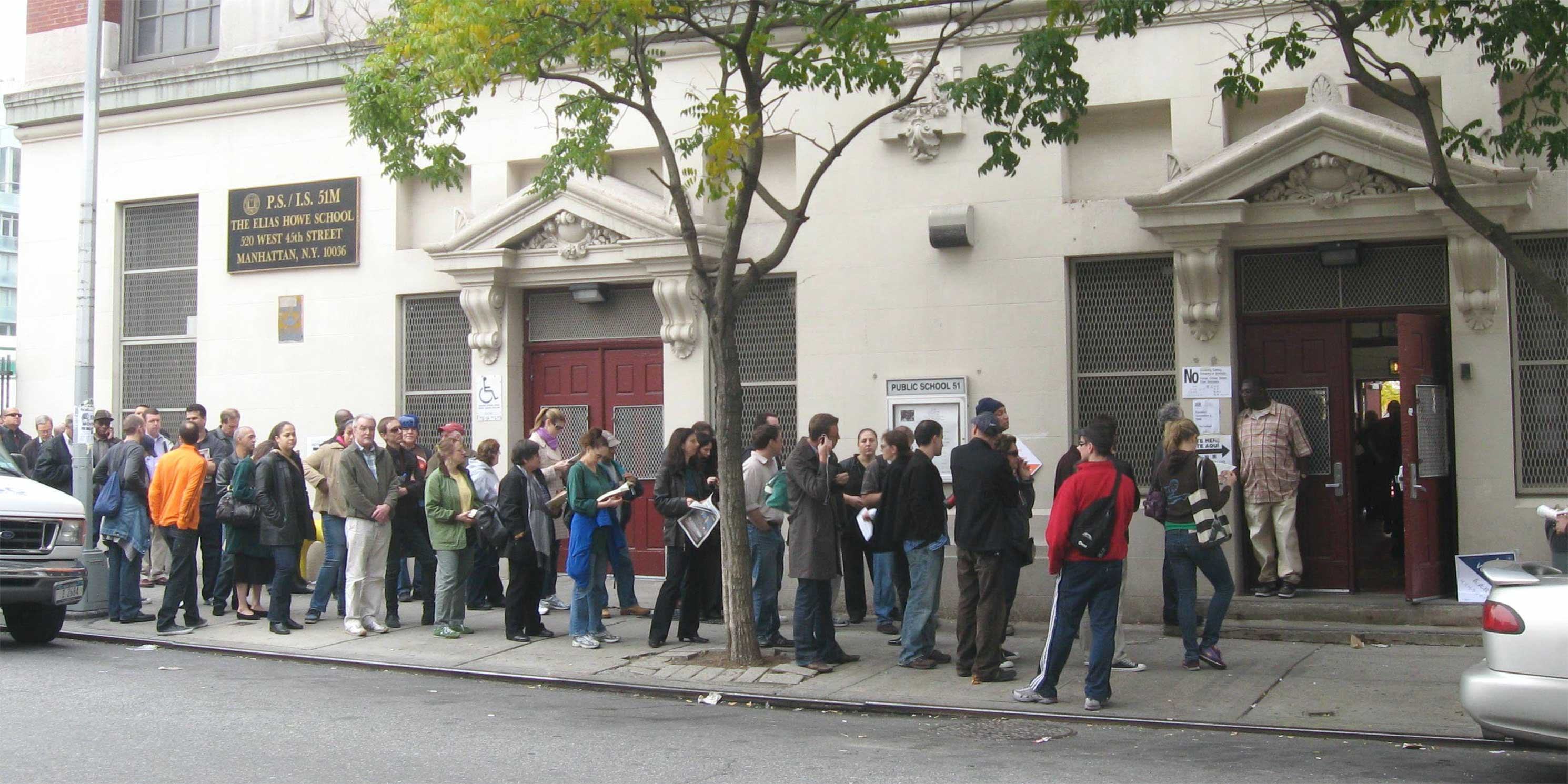 line of people waiting outside school to vote