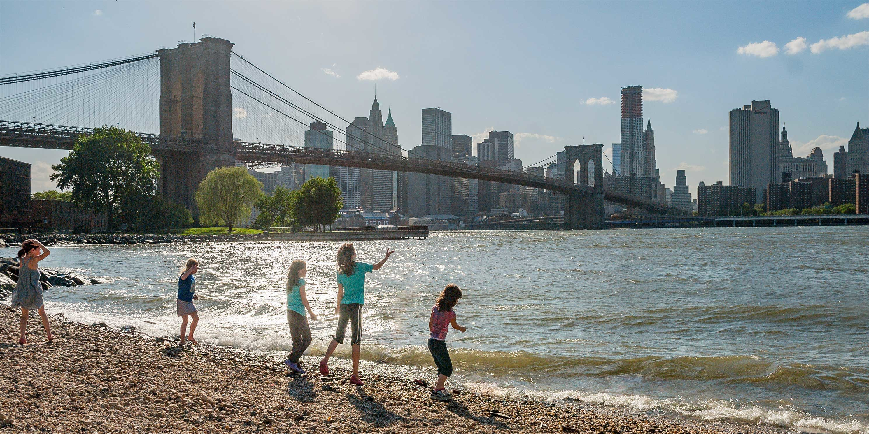 children play on the shore near the Brooklyn Bridge. Photo: Giles Ashford.