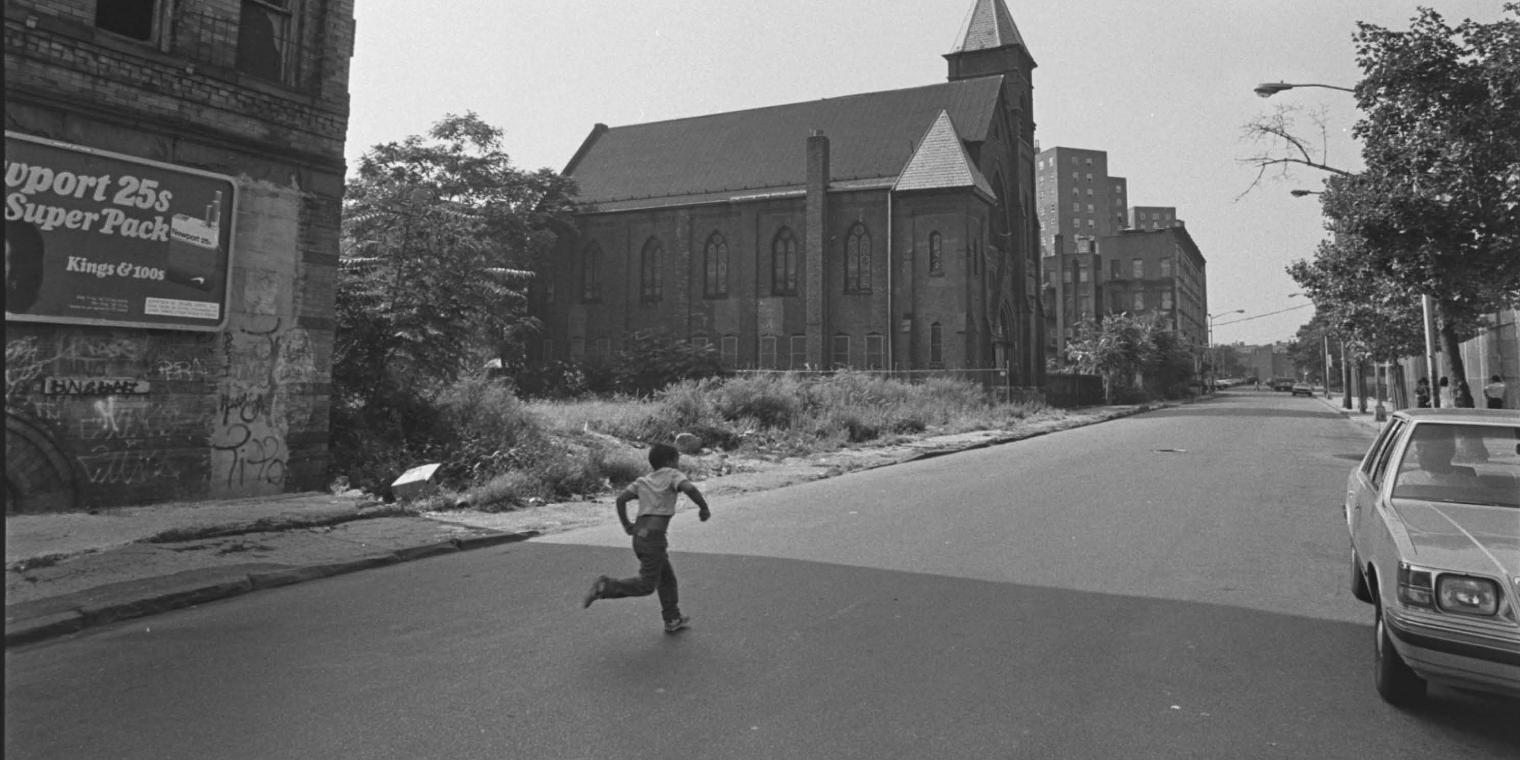 archival photo of a boy running on an empty Bronx street
