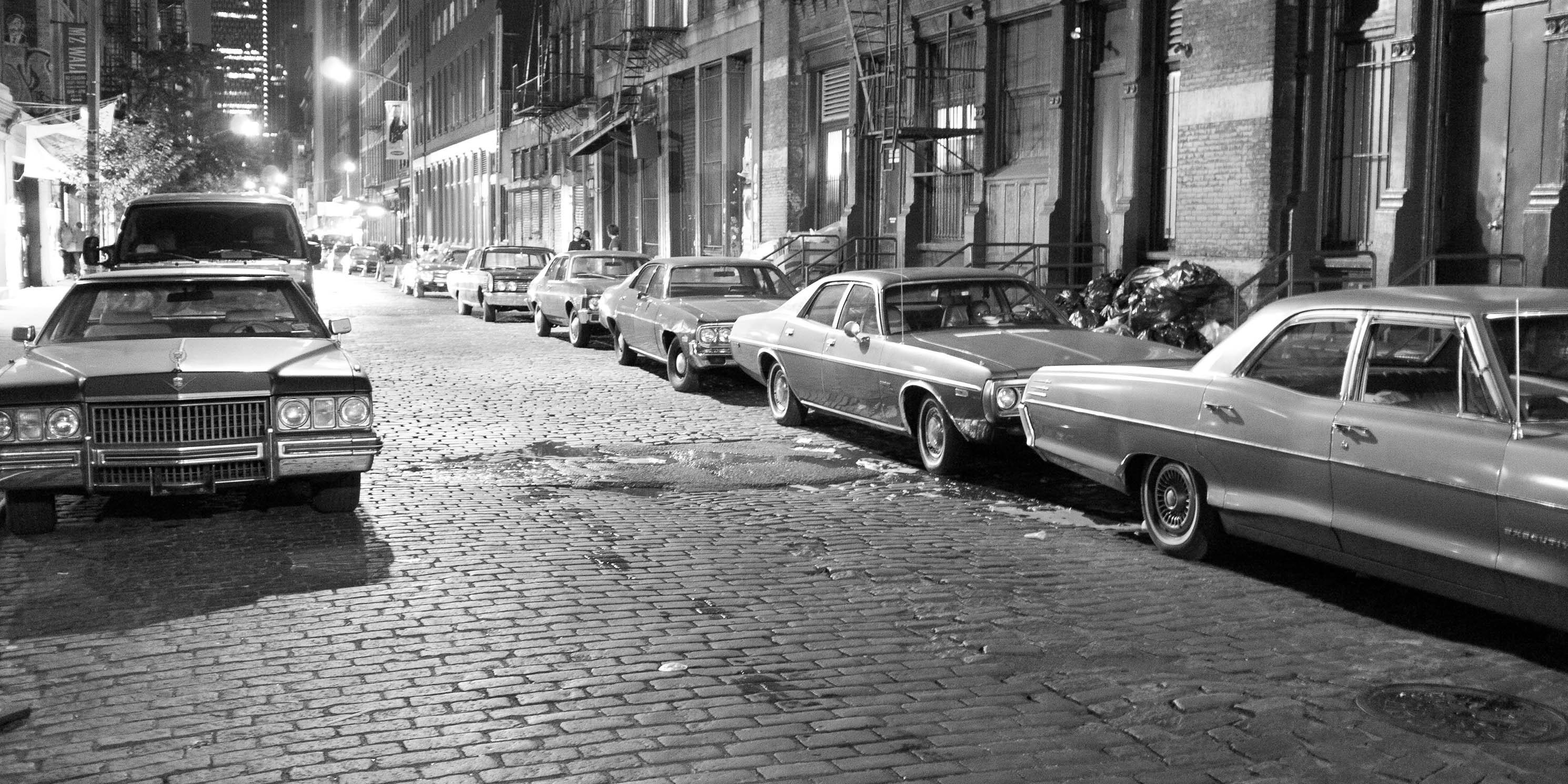 SoHo street at night, lined with cars from 1970's, part of a movie shoot