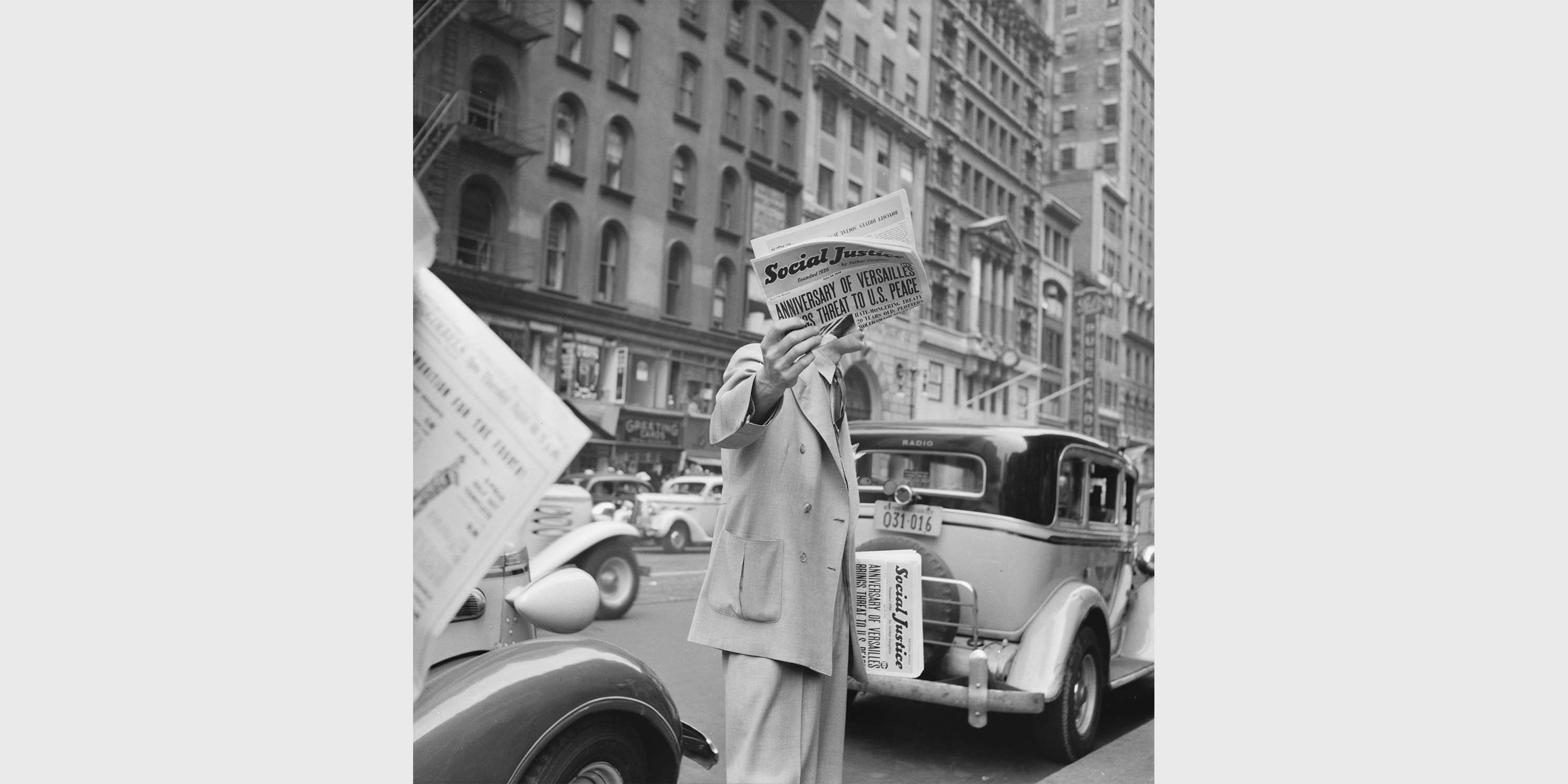 man sells Social Justice newspaper on New York City street, 1939