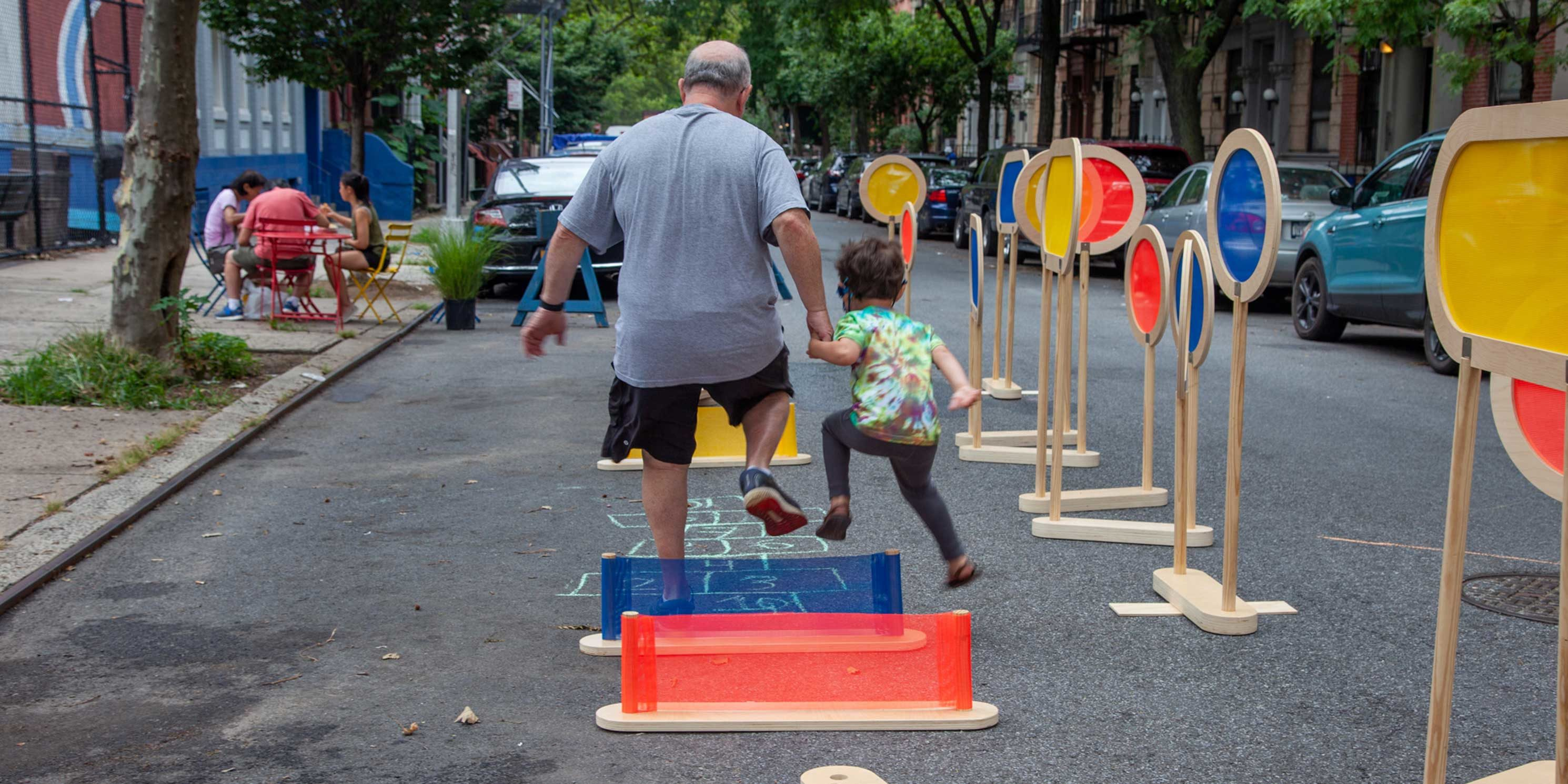 a father and child play on 101st Street in East Harlem during an Open Streets event