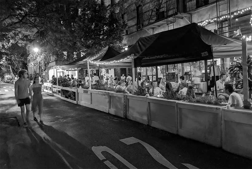 people enjoy night time outdoor dining during the COVID pandemic