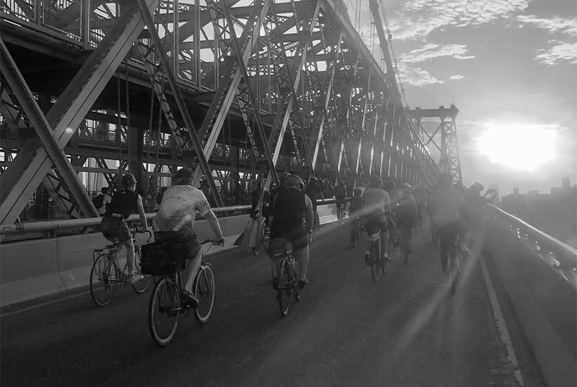 bicyclists ride across bridge in New York City