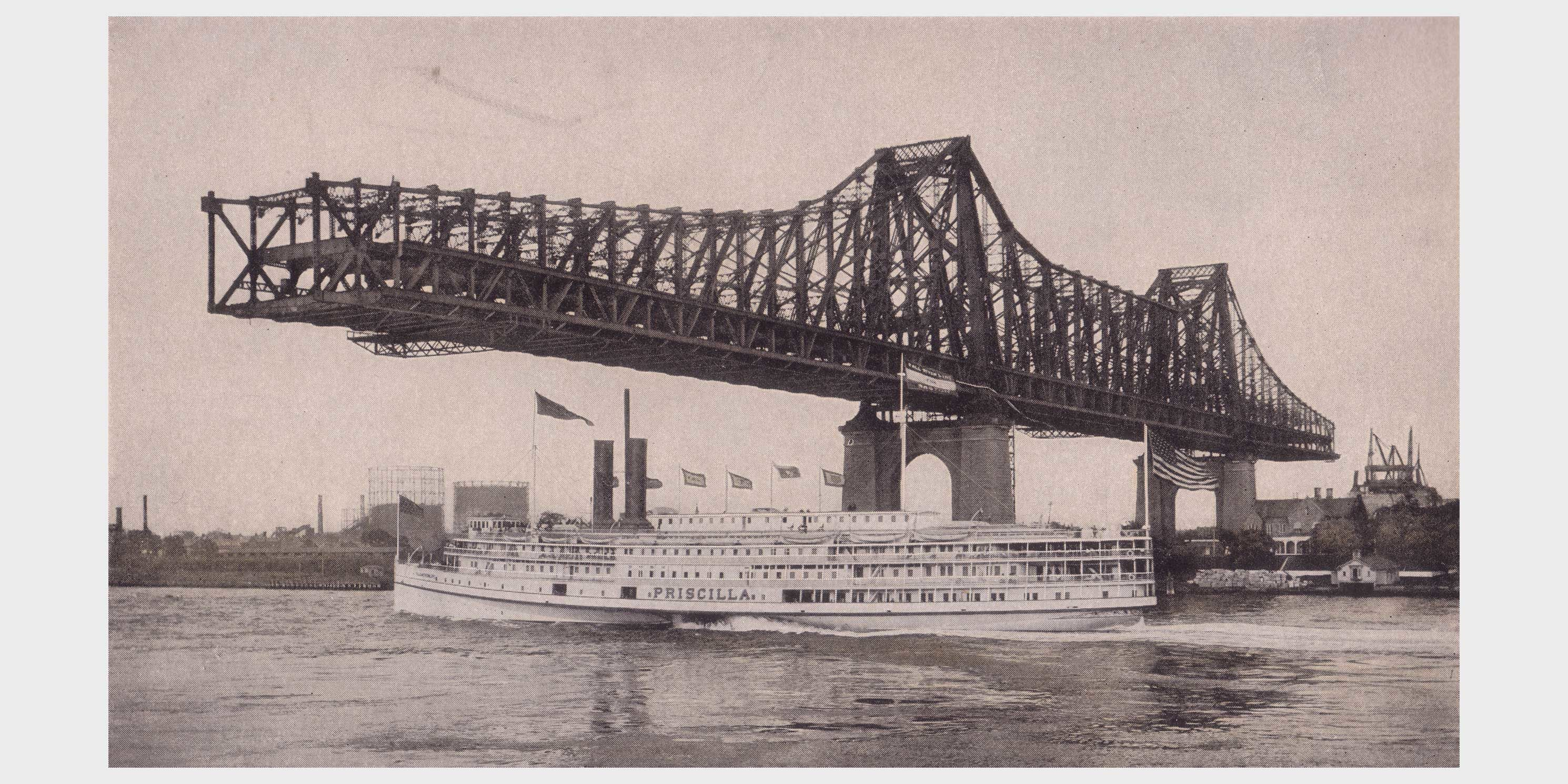 partially completed Queensborough Bridge with ferry passing under it