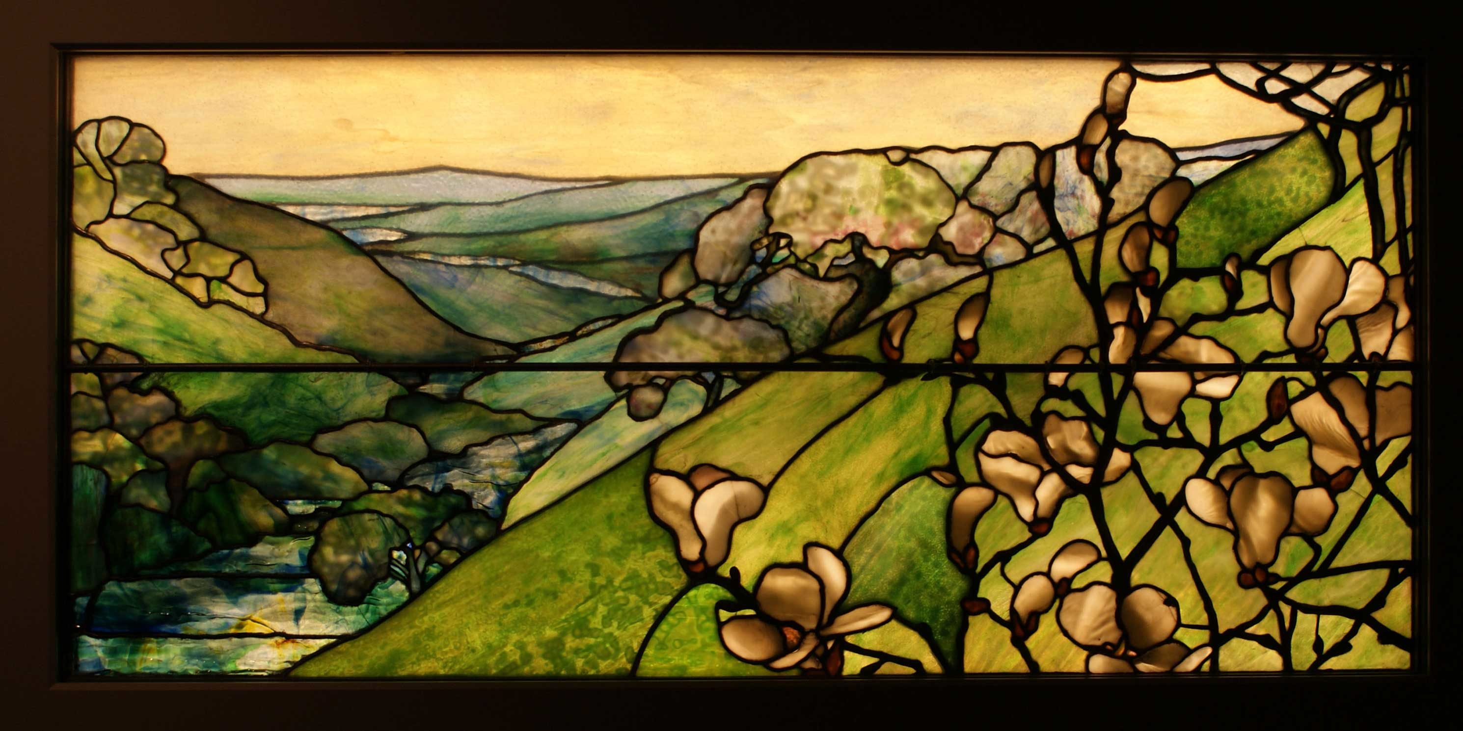 stained glass window featuring a landscape of green mountains