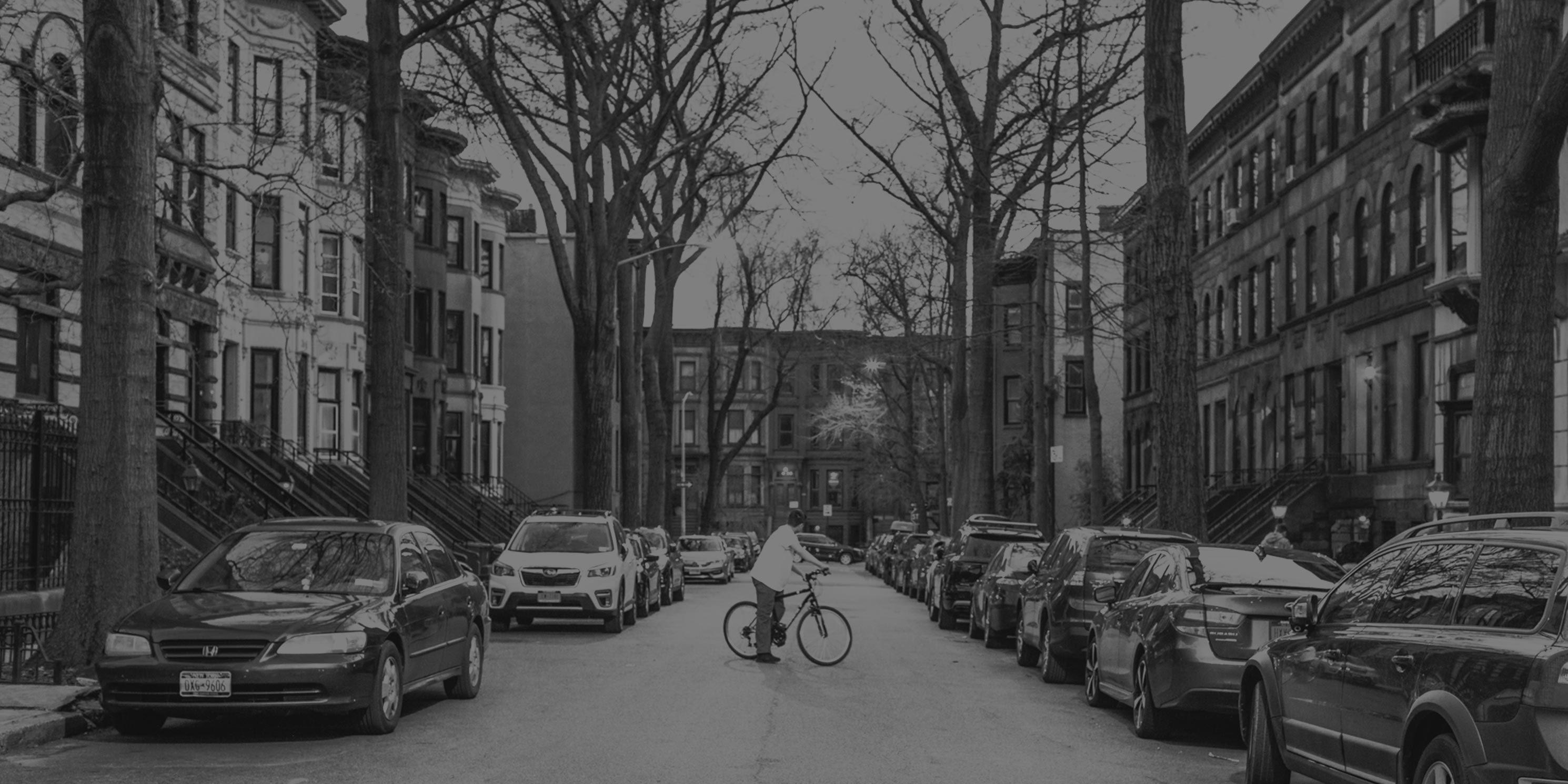 man rides bike on quiet street in Park Slope, Brooklyn