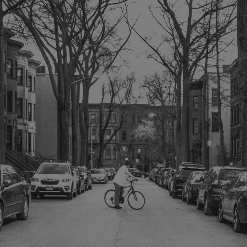 man rides bike on quiet street in Park Slope, Brooklyn