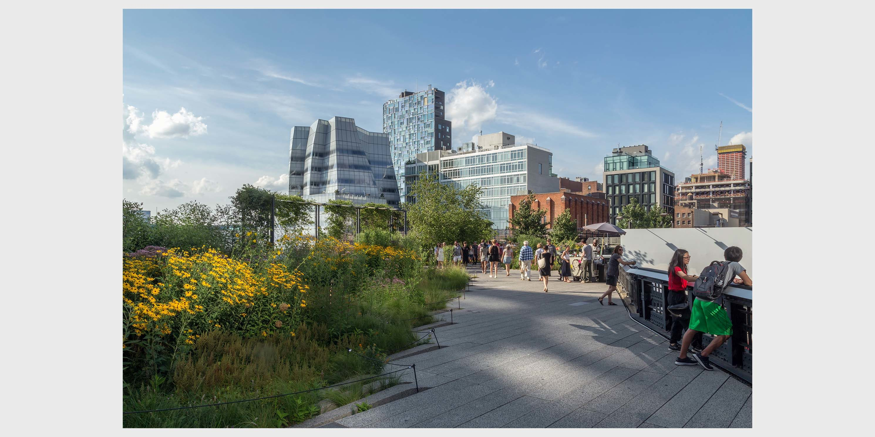 people stroll the Highline with IAC building in background