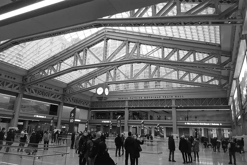 passengers stand inside the Daniel Patrick Moynihan Train Hall in Manhattan