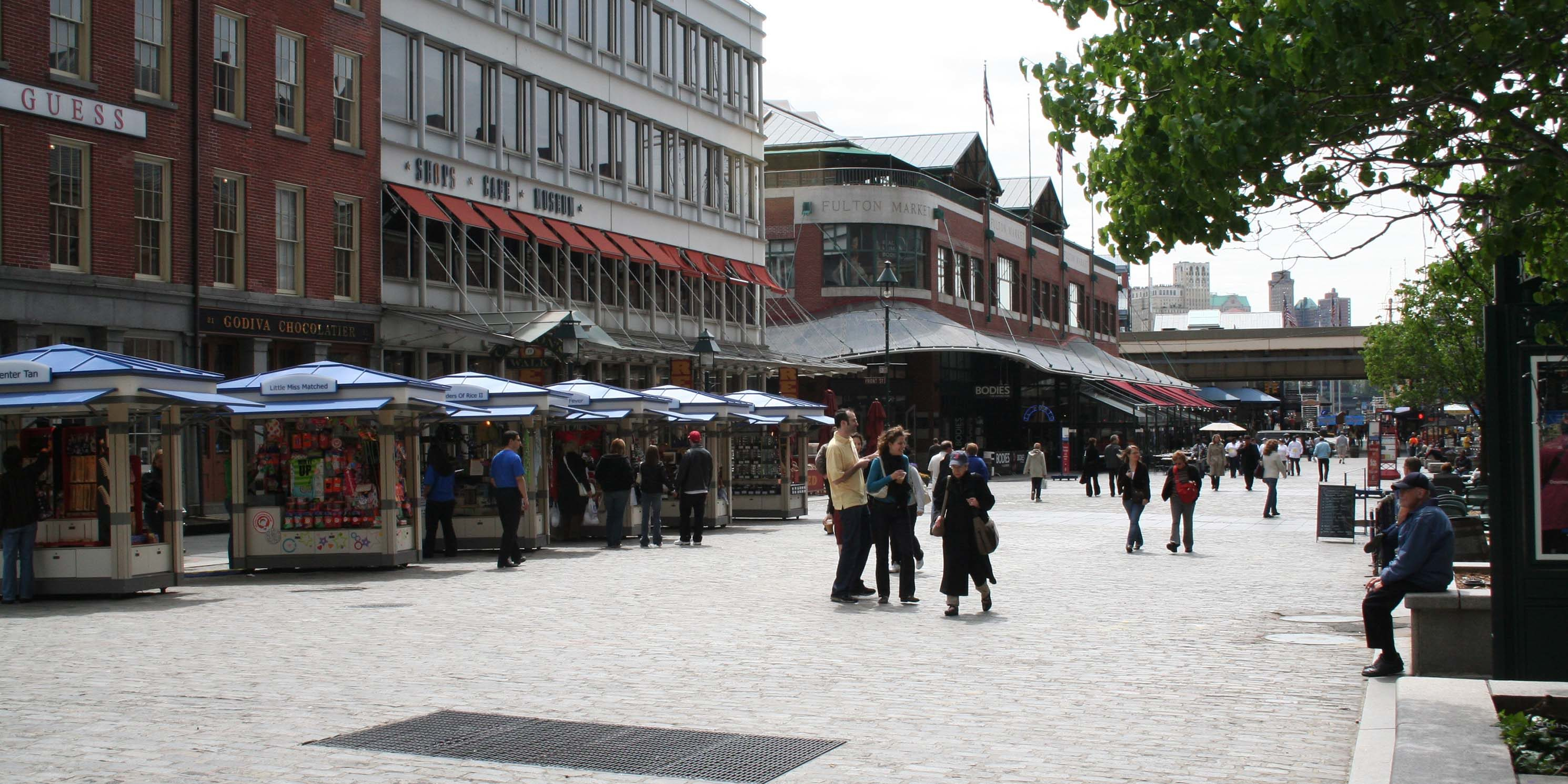 a cobblestone street with shops and kiosks at South Street Seaport