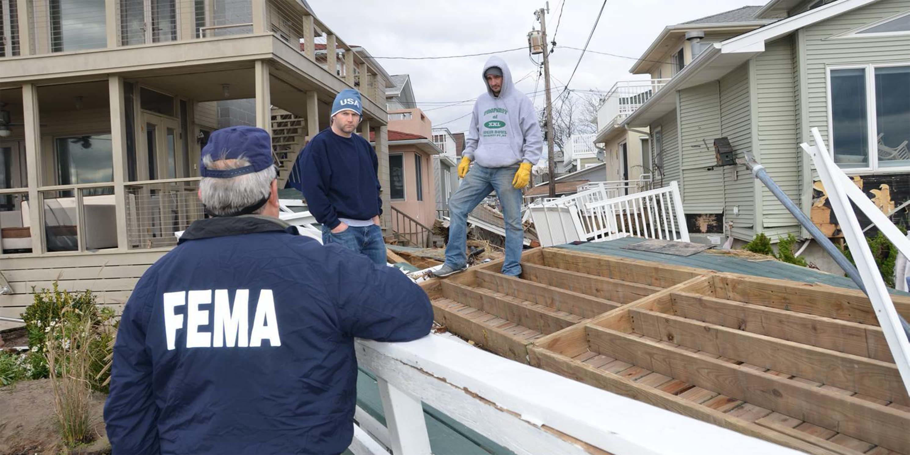 a Federal Office of Emergency Management official talks with Queen residents outside their damaged homes